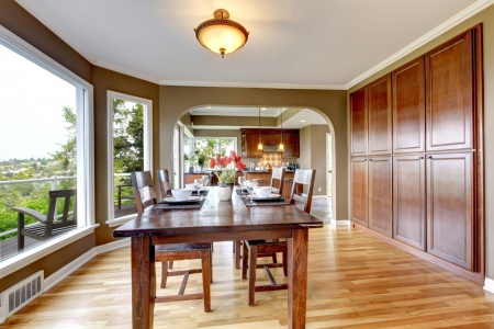 Luxury home dining room with large windows, wood and green. photo