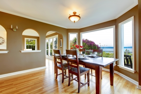 dining table and chairs: Dining room with brown walls and wood table with water view.