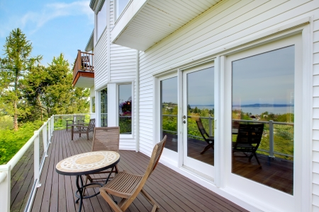13888949: White house balcony deck with furniture and large doors.