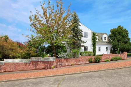 Large white American house with brick wall and street road. photo
