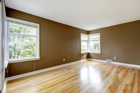 Empty room with brown walls and hardwood floor and two  windows. photo