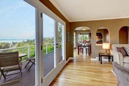 Luxury brown living room with hardwood floors and large balcony. Stock Photo