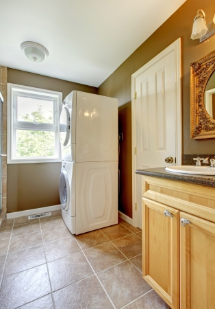Laundry room with bathroom cabinet and sink and ceramic tiles. photo