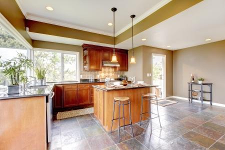 Lujo interior de la cocina con las paredes verdes y suelo de piedra y ventanas luminosas. Foto de archivo