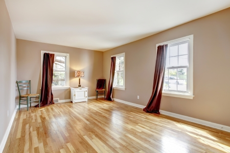 Beautiul empty bedroom with three windows and hardwood floor. photo