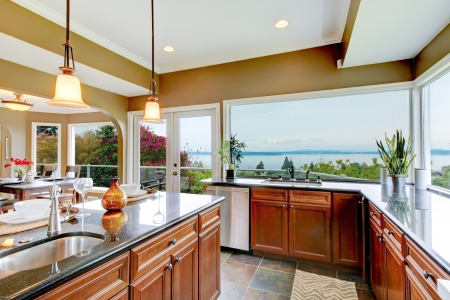 Modern luxury kitchen with water view, island and sink.