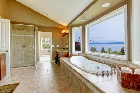 Large bath tun with water view and luxury bathroom interior in beige colors.