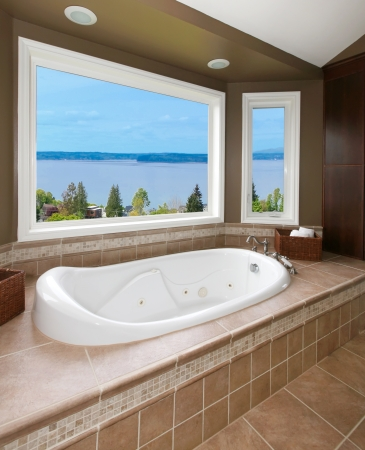 Brown bathroom with new tub and water view and beige tiles. Stock Photo