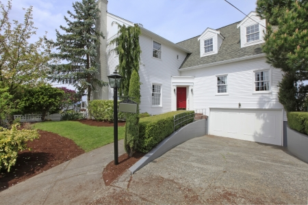 House colonial white with red door exterior front with large driveway. Stock Photo - 13888953
