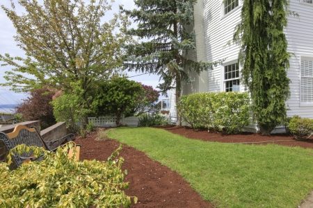 White houe and newly landscaped yard with fence and shrubs. photo