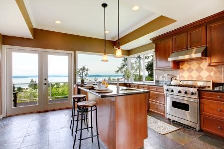 big windows: Роскошный интерьер кухни с зелеными стенами и каменным полом и видом на воду. Фото со стока