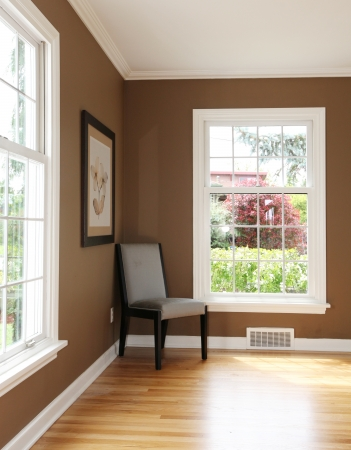 living room interior: Living room corner with chair and two windows and hardwood floor.