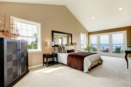 Beige classic large bedroom with water view and carpet. photo