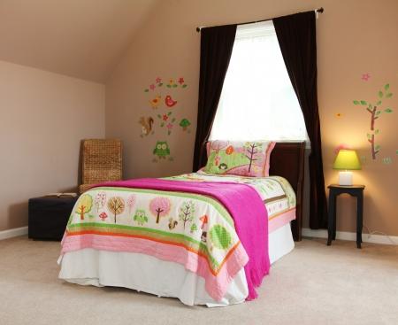 Roze bed in kinderen meisje slaapkamer interieur met bruine muren. Stockfoto