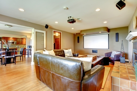 living room sofa: Large living room with brown walls and leather sofa with projector screen.