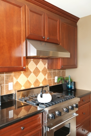 Luxury wooden kitchen with stainless steal stove and white tea pot. photo