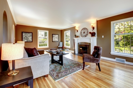 family living: Classic brown and white living room interior with hardwood floor.