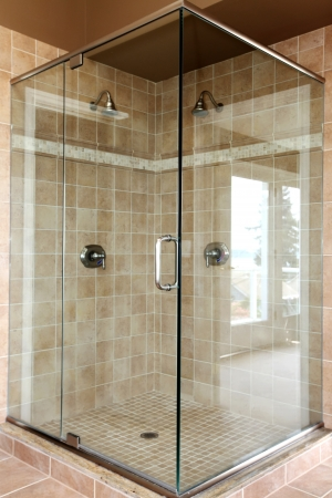 Modern new glass walk in shower with beige tiles and two heads. photo