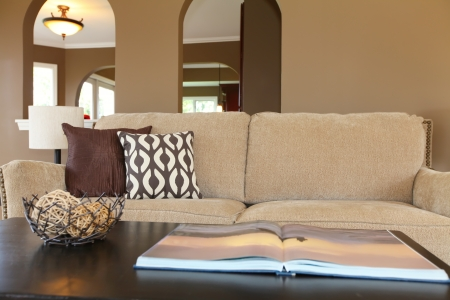 Beige sofa with black table and pillows and open book.
