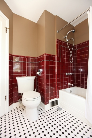 Classic antique brown and red bathroom with white toilet and red tiles. Stock Photo
