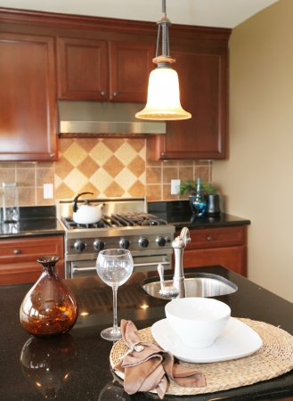 Kitchen granite countertop with plate and glass with stove and kitchen. photo