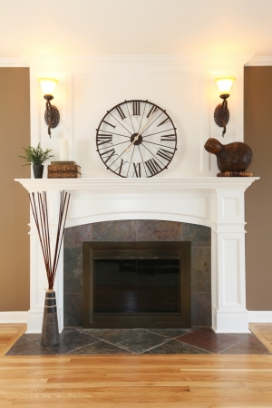 Luxury home white fireplace with stone, clock and brown walls. photo
