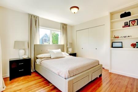 nightstand: White bedroom with hardwood cherry floor and black nightstand.