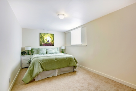 White large bedroom with green bed and art and beige carpet. photo