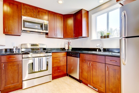 Modern new cherry kitchen with steal appliances.