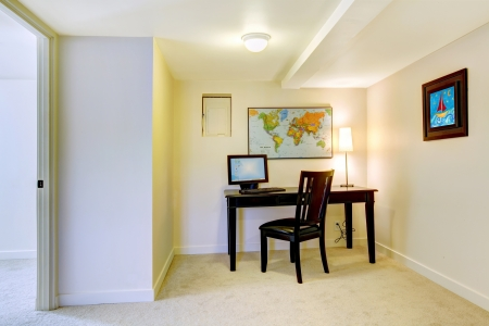 Home office desk with map on the white wall and art.