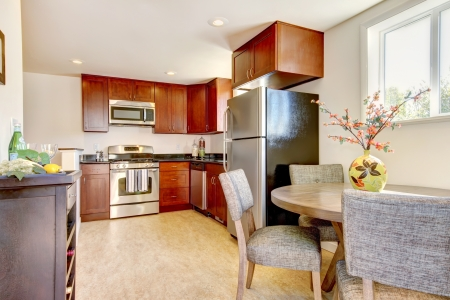 Beautiful cherry kitchen with stain steal apliances and dining room table. Stock Photo - 14032750