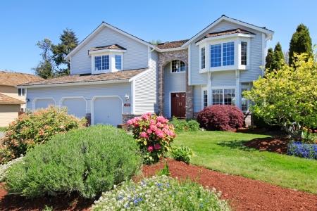 Grote Amerikaanse grijze huis voorbuitenkant met groen landschap.