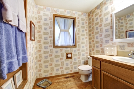 Simple old bathroom with brown and blue wallpaper. photo