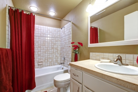 bathroom tiles: Small simple beige and red bathroom with white sink.