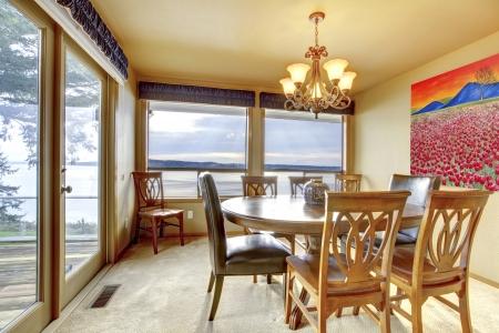 Eetkamer met beige muren, kunst en uitzicht op het water. Stockfoto