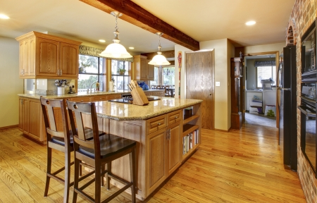back kitchen: Golden warm wood kitchen with large island and back appliances.