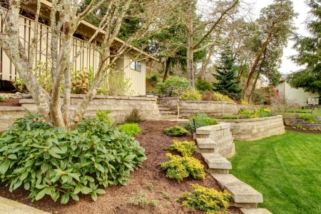 mulch: Early Spring Landscape with retaining walls and garage on the back.