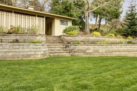 Retaining brick wall with garage building and spring landscape. photo