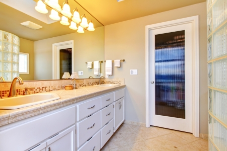 Large bathroom with white cabinets and glass shower and glass door. photo