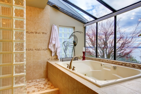 Large tub with glass wall and water view near shower. photo