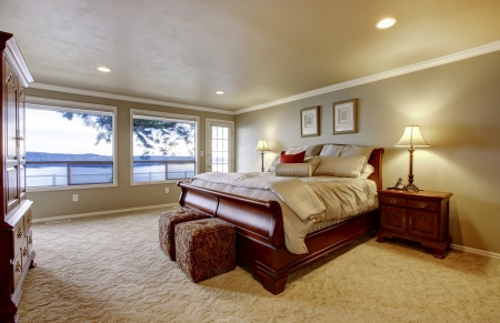 nightstand: Master bedroom wtih large bed and water view. Stock Photo