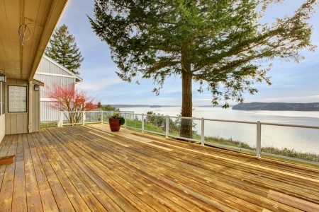 Large wood porch with glass railings and water view. Stock Photo - 14287749