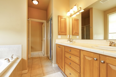 Bathroom interior with beige tiles and wood cabinets. photo