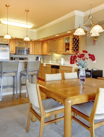 furnished apartments: Wood dining room table near kitchen in luxury apartment. Stock Photo