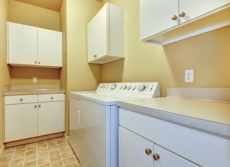 Simple laundry room with beige walls and white cabinets.