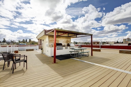 sitting area: Apartment building roof top deck with grill and sitting area.