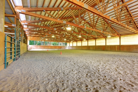 Large horse arena interior with wood beams. Stok Fotoğraf