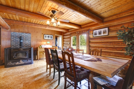 Log cabin ruustic living room with large table and stove. photo