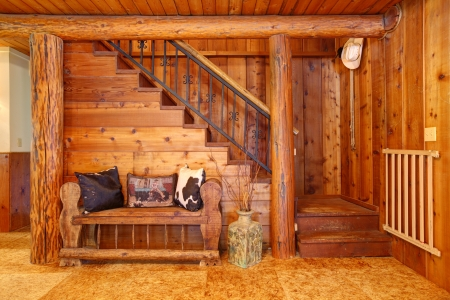 Rustic old log cabin details with staircase and wood bench. Stock Photo