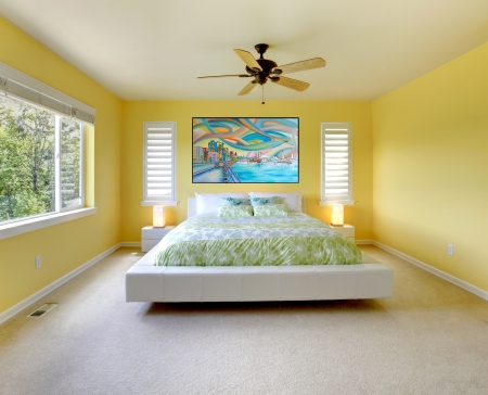 Yellow modern bedroom interior with white bed. photo